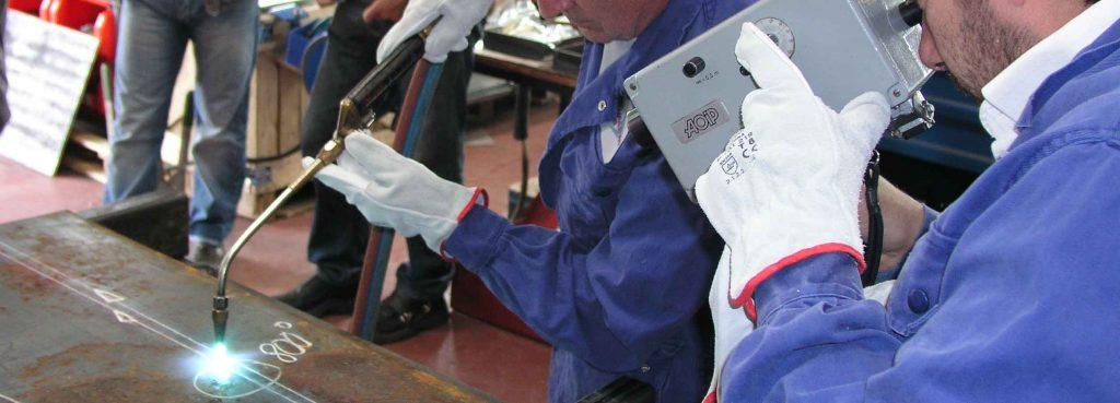 Deux opérateurs effectuent une chaude de retrait pour corriger une déformation sur un ensemble mécanosoudé